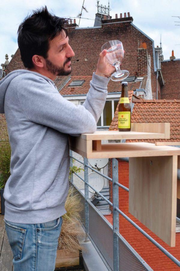 Vue du meuble positionné sur un garde corps de balcon. Utilisation du meuble en position bar avec un homme qui prend un verre pour trinquer.