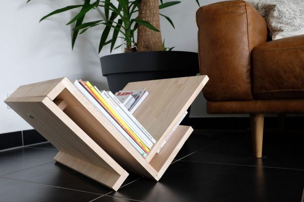 """Le meuble est posé au sol en """"V"""" et porte des revues."""