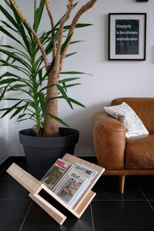 """Le meuble est posé au sol en """"V"""" et porte des revues dans un décor de salon."""