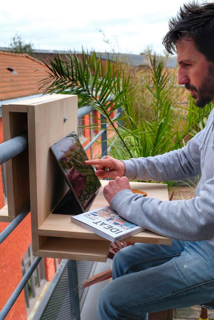 Vue du meuble positionné sur un garde corps de balcon. Utilisation du meuble en position tablette pour ordinateur. Un homme manipule un iPad