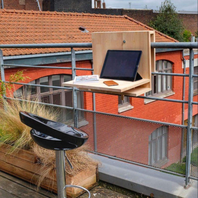 Vue du meuble positionné sur un garde corps de balcon. Utilisation du meuble en position tablette pour ordinateur.