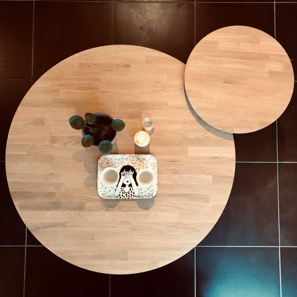 2 tables basse en cercle de 2 dimensions différentes. La plus petite est légèrement plus haute pour se superposer sur la plus grande. Pieds en trapèze métal noir.