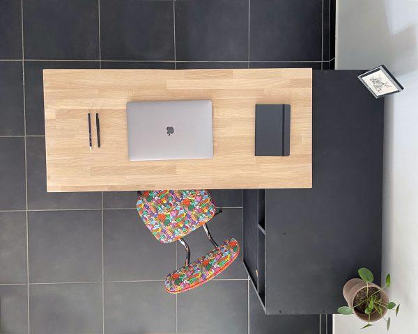 Bureau amovible noir avec tablette supérieure. Rangement bas en bois avec 2 portes coulissantes. Un plateau avec une joue latérale sur roulette est au dessus du rangement. Ce plateau en chêne naturel est pivotant pour se transformer en bureau.