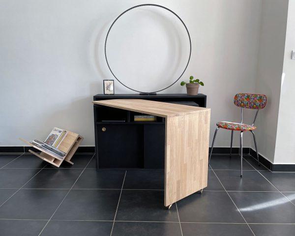 Bureau amovible noir avec tablette supérieure. Rangement bas en bois avec 2 portes coulissantes. Un plateau avec une joue latérale sur roulette est entre 2 planches en bois noires. Ce plateau en chêne naturel est pivotant pour se transformer en bureau.